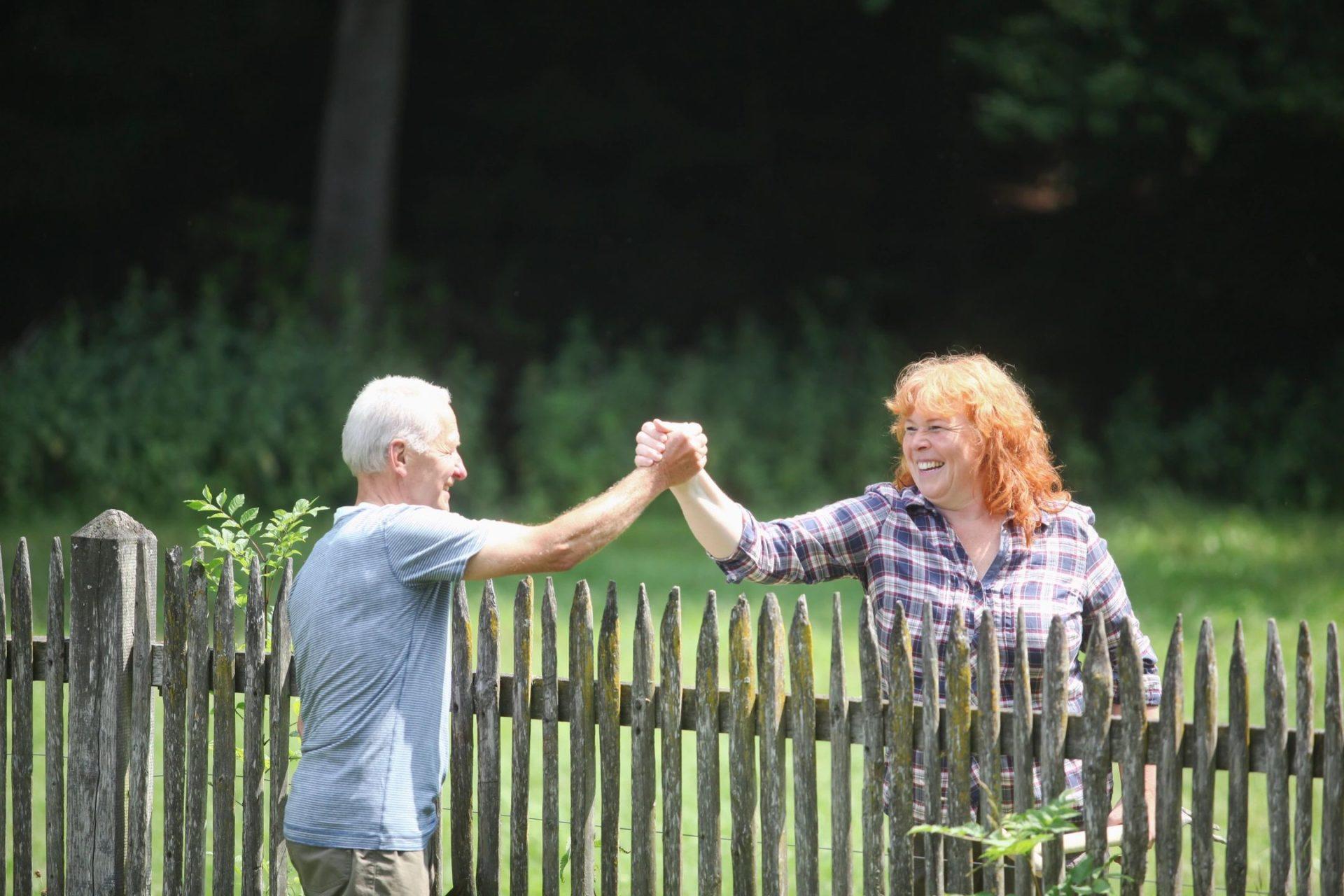 Two older people grabbing hands over fence smiling